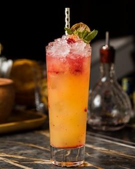 Cóctel de fresa y naranja con hielo picado, adornado con naranja seca