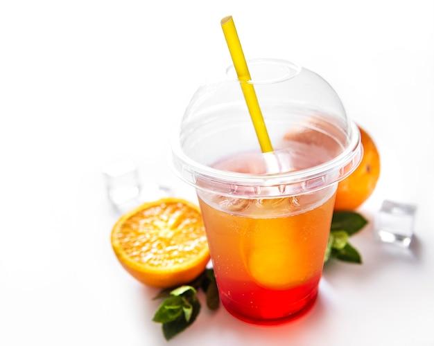 Cóctel fresco con naranja y hielo. bebida alcohólica, no alcohólica sobre una superficie blanca