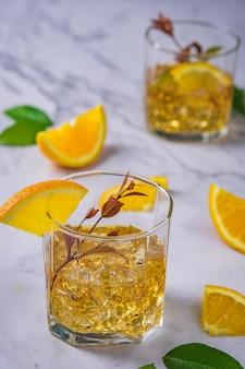 Cóctel fresco con naranja, menta y hielo, enfoque selectivo