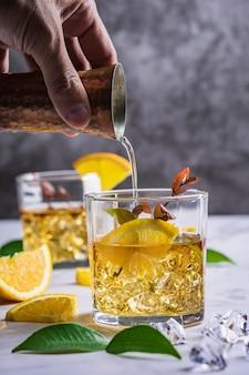 Cóctel fresco con naranja, menta y hielo.