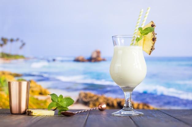 Cóctel frío de piña colada en un vaso en la playa con superficie marina