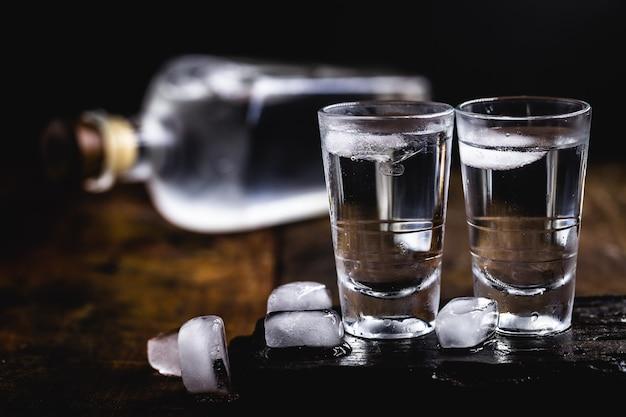 Cóctel frío con tónica, vodka y hielo en la madera