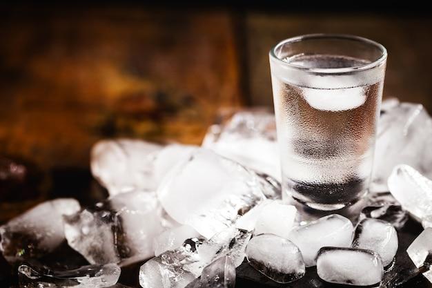 Cóctel frío con tónica, vodka y hielo sobre madera