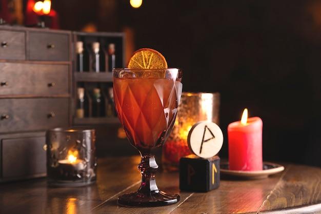 Cóctel de frutos rojos con decoración de limón, entre runas y velas