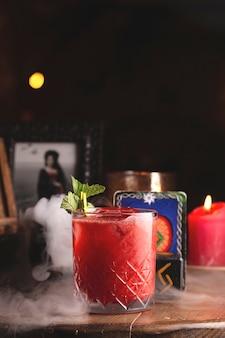 Cóctel de frutos rojos frescos con menta entre decoración de brujas, humo y velas