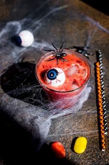 Cóctel de frutos rojos con hielo, ojos y arañas para fiesta de halloween con web