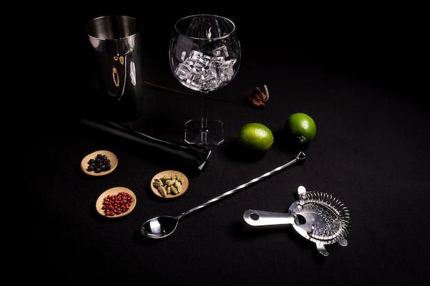Cóctel de ginebra y tónica sobre fondo negro con sus ingreedientes.