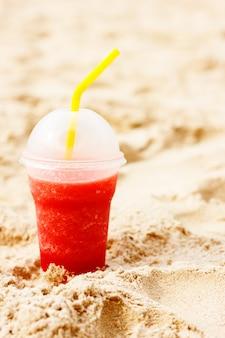 Cóctel helado de frutas rojas en la arena de la playa