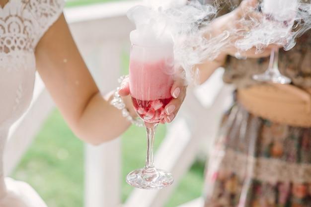 Cóctel humeante con hielo seco en la mano