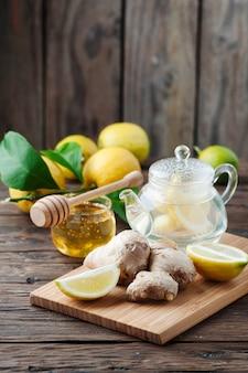 Cóctel con jengibre, limón y miel sobre la mesa de madera.