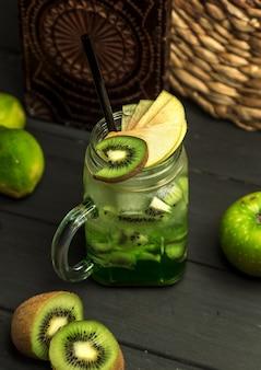Cóctel de kiwi adornado con rodajas de kiwi y manzana