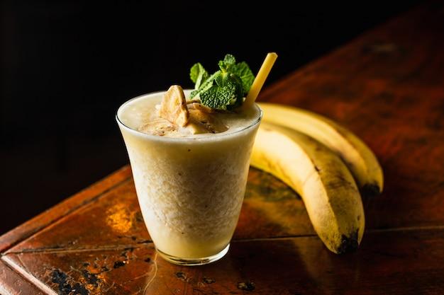 Cóctel de licuado de plátano adornado con menta y chips de plátano