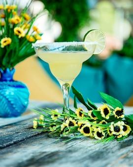 Cóctel de lima adornado con rodaja de lima en vidrio decorado con chispas de azúcar