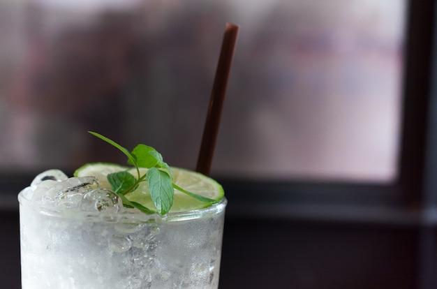 Cóctel con limón y hielo sobre un fondo claro.