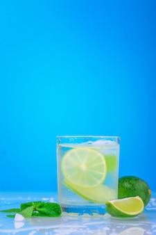 Cóctel con limón y menta fresca en vidrio sobre un fondo azul