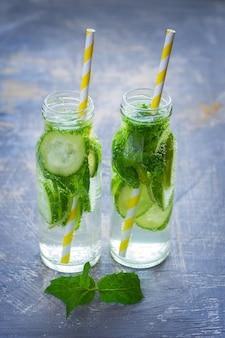 Cóctel de limón, menta, pepino en botellas de vidrio
