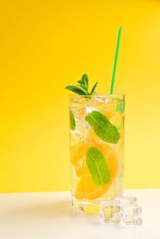 Cóctel con limón y menta sobre amarillo