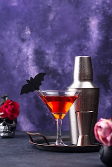Cóctel de martini de halloween sobre fondo morado