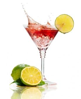 Cóctel de martini rojo con salpicaduras y limón aislado