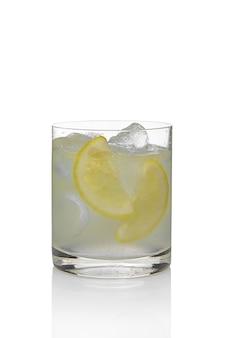 Cóctel martini y tónico con el limón y el hielo aislados en blanco.