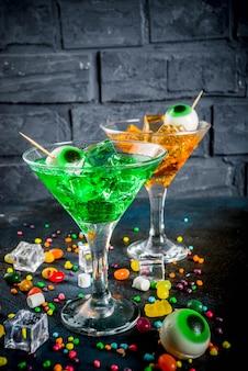 Cóctel de martini verde y naranja con cubitos de hielo y una decoración de ojos malvaviscos