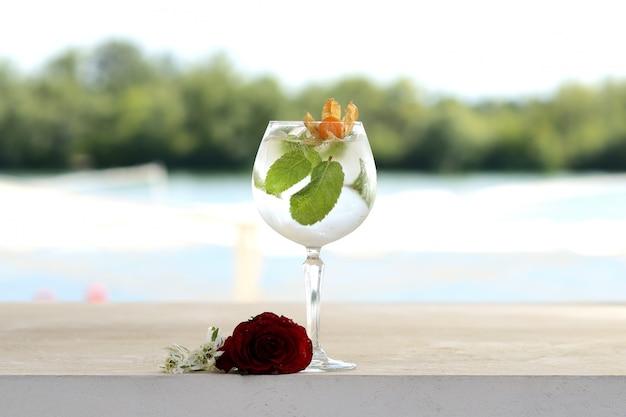 Cóctel con menta y hielo en un vaso de vidrio. con decoración de flores y frutas.