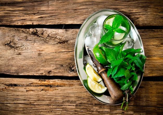 Coctel mojito. cóctel fresco de limón, menta, ron y hielo en una bandeja de metal sobre una mesa de madera. vista superior