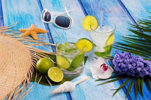 Cóctel de mojito cubano en flores de madera azul tropical