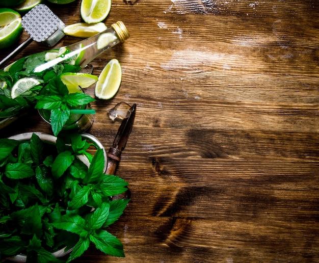 Coctel mojito. los ingredientes para el cóctel: limas, ron, hojas de menta, cubitos de hielo en la mesa de madera.vista superior