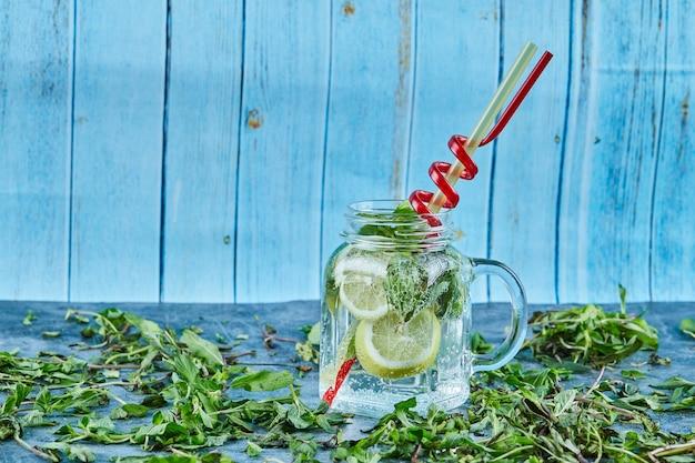 Cóctel mojito con rodajas de limón y menta en mesa azul con hojas de menta fresca
