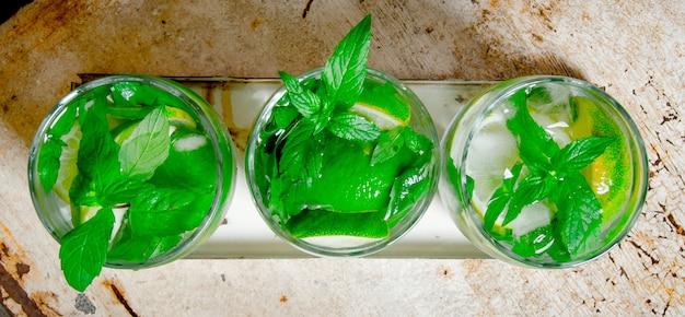 Coctel mojito. tres copas de cóctel con cubitos de hielo, limón, hojas de menta y ron en la mesa rústica. vista superior
