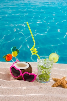 Coctel de mojitos en la arena de la playa con coco y gafas de sol.