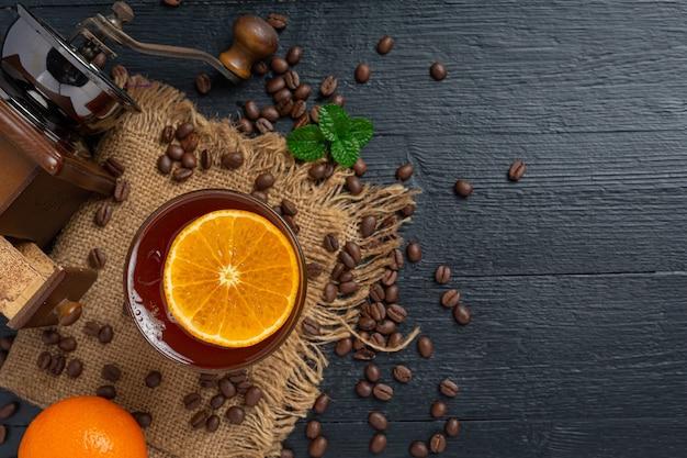Cóctel de naranja y café en la superficie oscura.