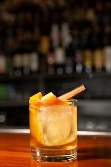 Cóctel de naranja con cubito de hielo y ralladura de naranja. en el vaso hay una ramita de canela, de la que sale humo.