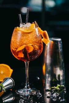 Cóctel de naranja dentro de vidrio con cubitos de hielo picado y tuberías.