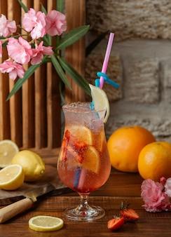 Cóctel de naranja y fresa con rodajas de fresa y naranja y hielo.