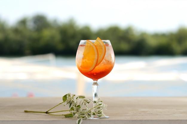 Cóctel con naranja y hielo en un vaso de vidrio. con decoración floral