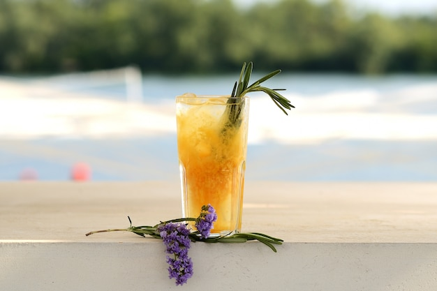 Cóctel de naranja en un vaso. con decoración floral