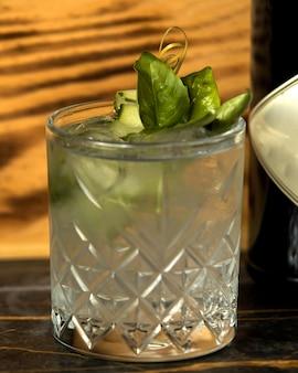 Cóctel de pepino en cristal adornado con hojas de albahaca