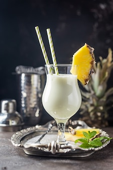 Cóctel de piña colada congelada casera con ron, leche de coco y guarnición de piña sobre superficie negra