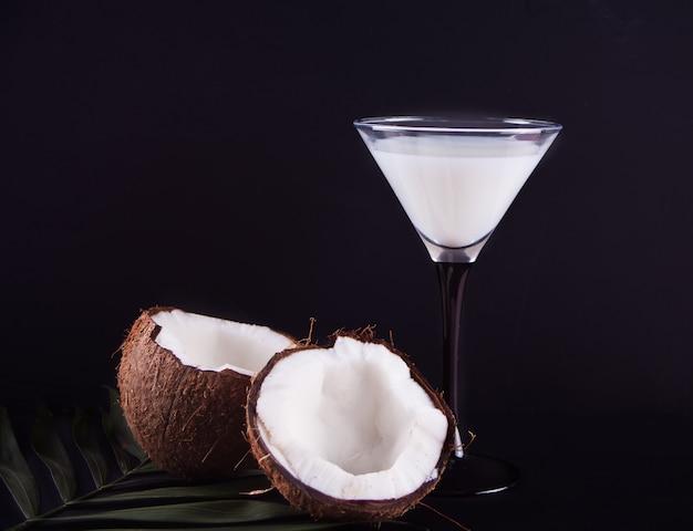 Cóctel de piña colada con hoja de palma y coco en el fondo negro