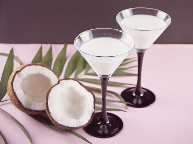 Cóctel de piña colada con hoja de palma y coco en el fondo.