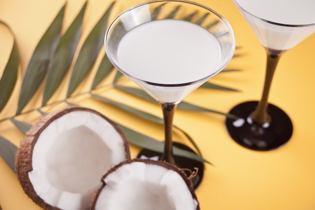 Cóctel de piña colada en la mesa amarilla con hoja de palma y coco en el fondo
