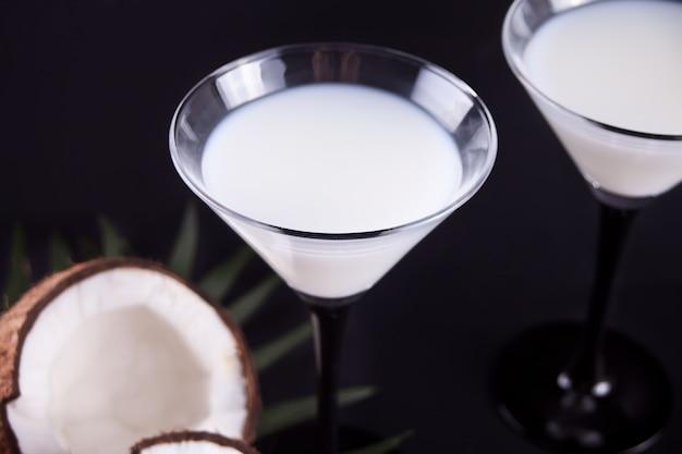 Cóctel de piña colada en la mesa negra con hoja de palma y coco en el fondo