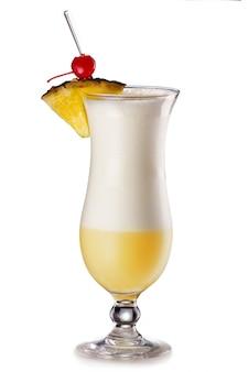 Cóctel de piña colada con una rodaja de piña y cereza aislados.