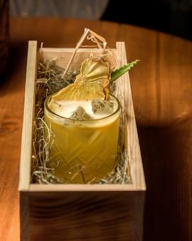Cóctel de piña con hielo y piña seca servida en caja de madera con forraje