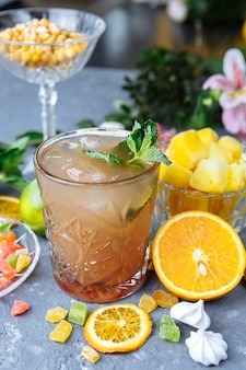 Cóctel de piña refrescante frío con limón y menta para un caluroso día de verano en un gris