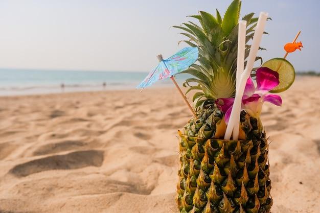 Cóctel de piña tropical piña fresca tumbada en el fondo de la playa de arena
