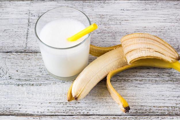 Cóctel de plátano y plátanos frescos en madera