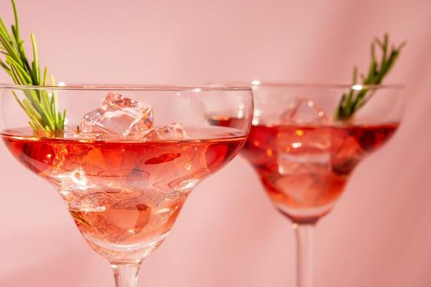 Cóctel refrescante con romero en un vaso sobre un fondo brillante.